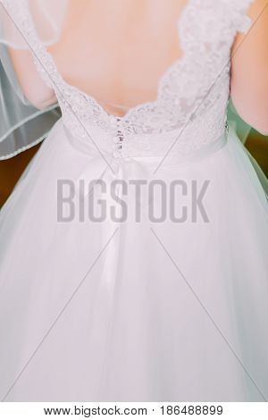 Close up of traditional white wedding dress at the back.