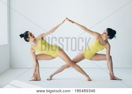 Two Beautiful Women Doing Yoga Asana Extended Side Angle Pose