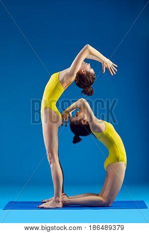 Two Young Women Doing Yoga Asana Standing Backbend Pose