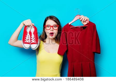 Young Woman With Dress On Hanger And Gumshoes