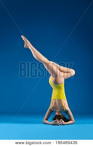 Young woman doing yoga asana supported headstand Salamba Sirsasana variation