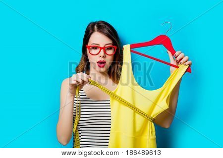 Young Woman With Dress On Hanger And Centimeter