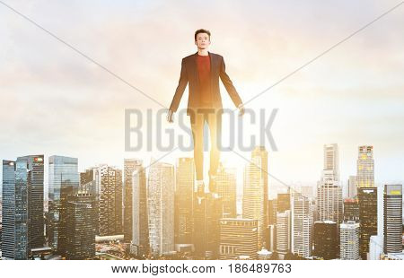 Businessman hovering over down town on sunset.