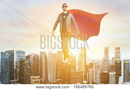 Business superhero. Businessman in sketch super hero suit hovering over down town on sunset.