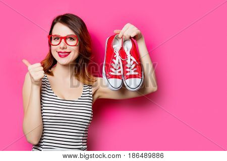 portrait of beautiful smiling young woman with gumshoes on the wonderful pink studio background