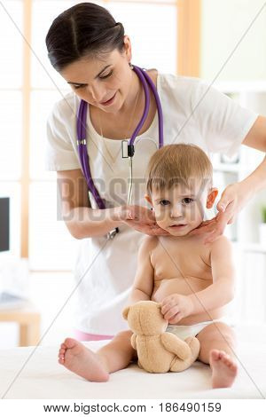 Pediatrician doctor touching the throat of child patient in medical office