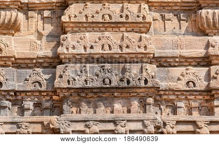 Ancient design of stone relief on wall of 7th century temple in Pattadakal of Karnataka, India. UNESCO World Heritage site with stone carved temples.