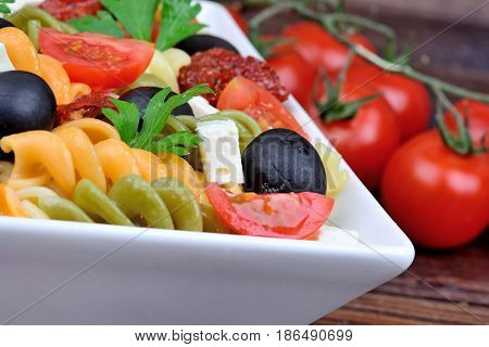 Fusilli with tomato cheese and olive in a bowl on table