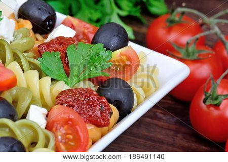Fusilli with tomato olive and cheese in a plate on wooden table