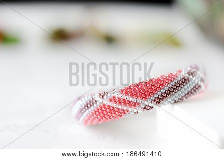 Bead Crochet Bracelet Made Of Red And Brown Beads On A Textile Background