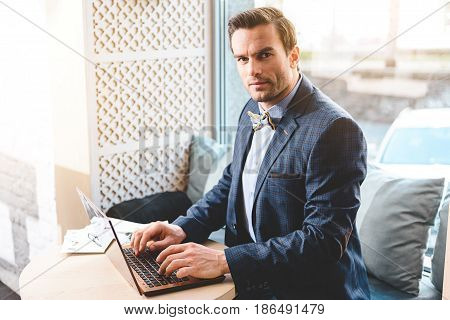 I like my job. Portrait of serious stubbled male working on laptop while situating in cozy office. He looking at table