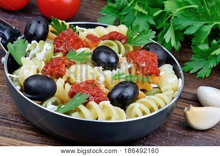 Colorful fusilli with vegetable in a pan on table