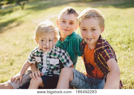 Outdoor portrait of three happy brothers at sunset. Boys are posing and looking at the camera