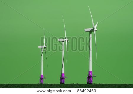 Green Energy Production. Three offshore wind turbines in profile against color manipulated background.