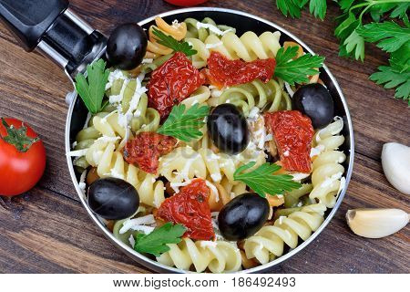 Pasta with cheese dried tomato and cheese in a pan on table