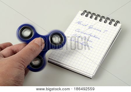 Blue Hand spinner fidgeting hand toy and words written : concentration stimulation and antistress