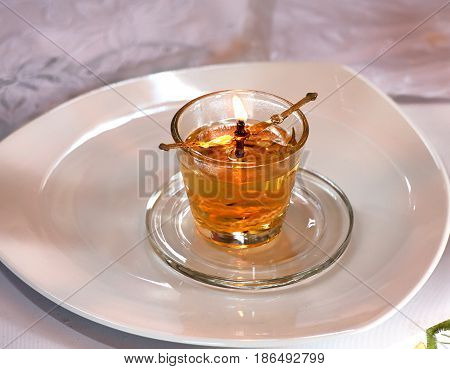 Burning oil glass clear lamp in the temple which is on a glass saucer and a white plate