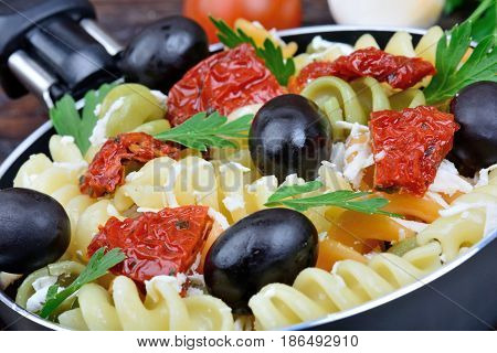 Colorful fusilli with vegetable in a pan on wooden background