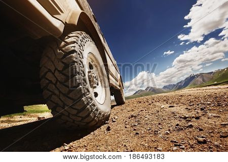 Bottom view to big offroad car wheel on country road and mountains backdrop. Space for text