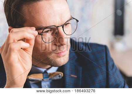 Portrait of smart bristled man expressing composure. He looking away while locating in room