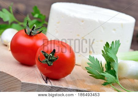 Tomatoes with cheese parsley and onion on wooden background