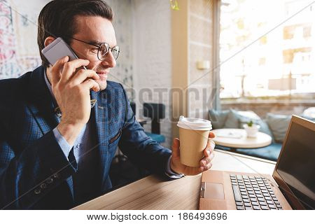 Side view smiling bristled businessman telling at mobile while drinking plastic glass of coffee in apartment