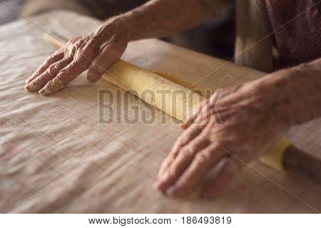 Detail of an elderly woman's hand rolling out a dough with a rolling pin while making homemade pasta. Selective focus