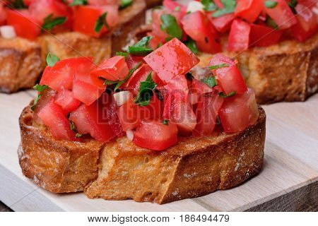 Bruschetta with tomatoes and garlic on chopping wooden board closeup