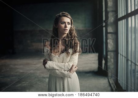 Beautiful Girl In In White Vintage Dress With Curly Hair Posing Near The Loft Window. Woman In Retro
