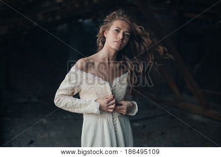 Beautiful Girl In In White Vintage Dress With Curly Hair Posing On The Attic. Woman In Retro Dress.