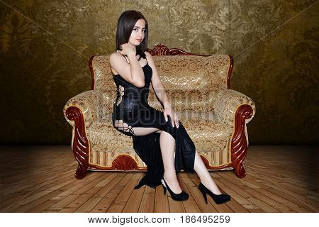 photography with scene of the sexual girl in black gown sitting on small sofa