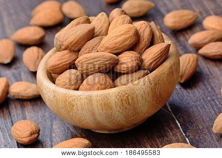 Almonds in a bowl on wooden table