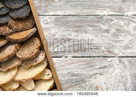 Bakery, bread gradient background on wood. Grocery concept with copy space. Black, rye and white loaves