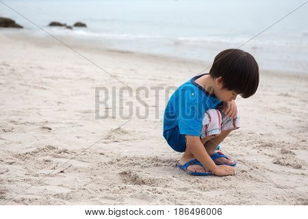 4 years old Asian boy sand writing lonely on beach at Hua Hin Thailand with sea background and copy space