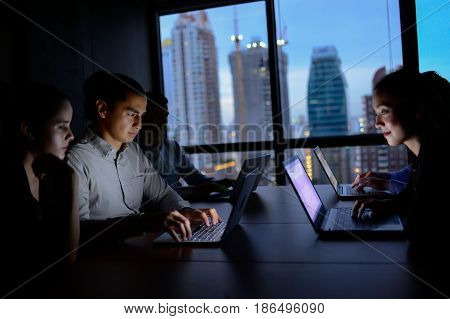 business team working with computer overtime at night and low light