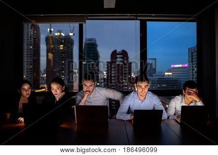 business team three man and two woman working with computer overtime at night and low light