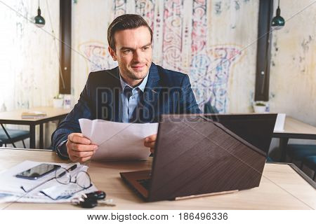 Smiling bristled smart man working with documents and notebook computer while sitting at table in cozy cafe