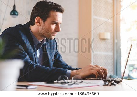 Side view of restrained bristled businessman typing on keyboard of notebook computer while sitting at table in room
