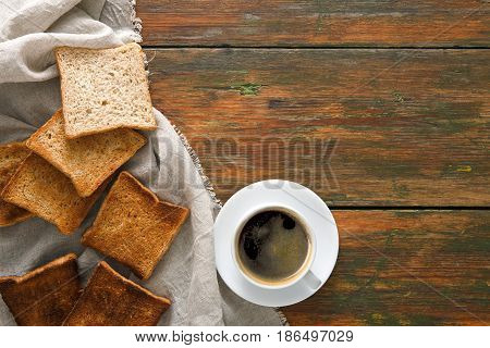 Breakfast background, toast and coffee on rustic wood, top view with copy space. Espresso and bread