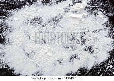 Abstract background. Wheat flour on black. Top view on blackboard. Baking concept, cooking dough or pastry.