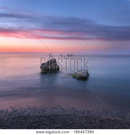 Amazing sunrise at the sea. Beautiful landscape with blue water stones and colorful sky with clouds in summer morning. Seascape. Tranquil scene. Nature background