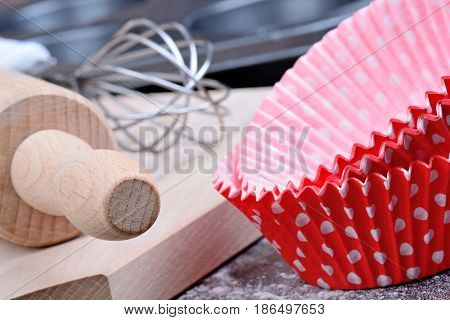 Utensils for muffins on wooden table close-up