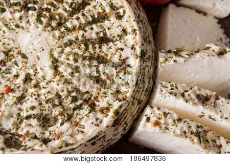 Homemade indian soft cheese paneer with herbs closeup, top view