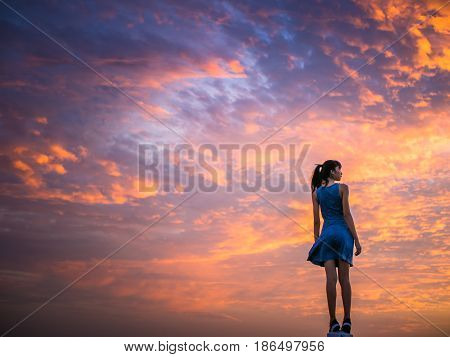 woman standing with beautiful dramatic of cloud