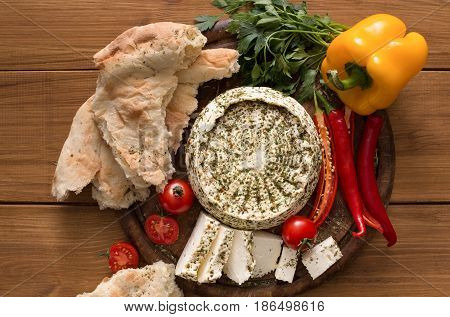 Homemade indian soft cheese paneer with herbs on wooden board with fresh vegetables and bread, top view