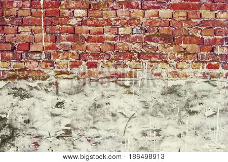 Half-plastered brick wall. Grunge brick wall half plastered. Half weathered brick wall a lot of copy space.Cracked wall. Aged architecture detail.