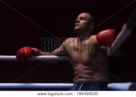 muscular professional kick boxer resting on the ropes in the corner of the ring while training for the next match
