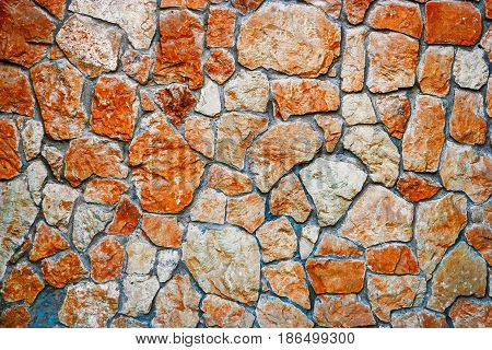 Stone wall exterior of the building covered with wild stone tiles brown color.