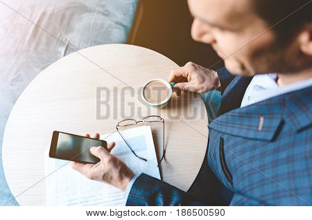 Top view happy stubbled male drinking cup of appetizing coffee while looking at cellphone