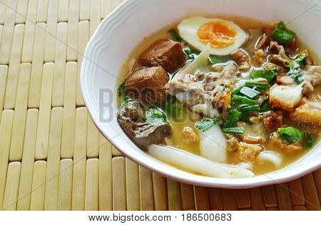 boiled Chinese pasta with pork and entrails topping creamy egg yolk in soup